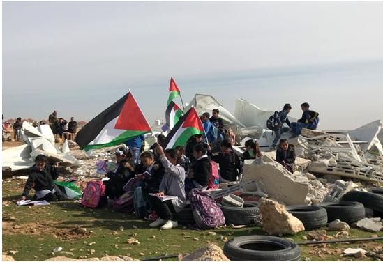 Palestinian children from the school in the Bedouin community of Abu an-Nuwar in the West Bank demonstrate seated on the ruins of their classrooms after their demolition by Israel, Sunday February 4.