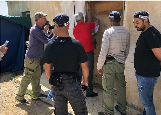 An Israeli official accompanied by armed police pins an eviction order on the front door of a home in the Arab-Bedouin village of Umm al-Hiran in the Negev.