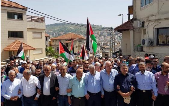 Palestinian-Arab citizens of Israel demonstrate en masse in the Galilean city of Sakhnin to protest the second consecutive Friday massacre of civilians along the Gaza border by the Israeli army, Saturday April 7, 2018. Among the protestors were former Hadash MK, Mohammad Barakeh, chair of the High Follow-Up Committee for Arab Citizens of Israel (third from left) and (third from right) Hadash MK Yousef Jabareenn.