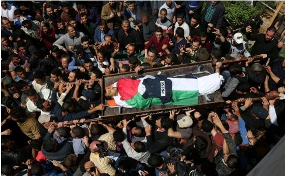 The body of Palestinian journalist Yasser Mortaja, 30, shot dead by an Israeli military sniper on Friday, April 6, is borne by Gazans to his grave.