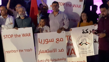 "Demonstration by Hadash and Communist Party of Israel (CPI) activists in Haifa Saturday evening, April 14, against the Washington-led missile strikes on Syria targets that were waged before dawn. The sign in Arabic in the center, held by CPI Secretary General Adel Amer, reads: ""With Syria against Imperialism, Zionism, and [Arab] Reactionism"""