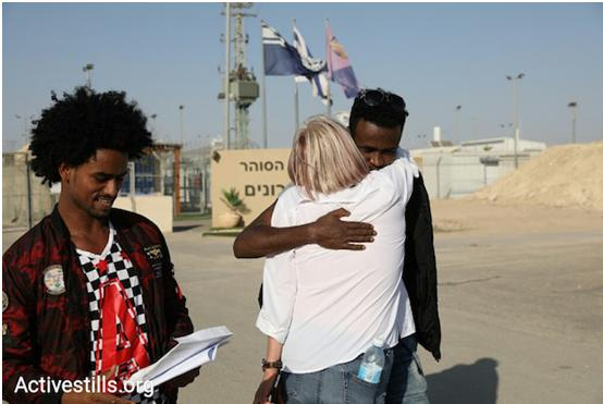 African asylum seekers and an Israeli activist outside of Saharonim Prison in the Negev after Israel released 207 asylum seekers incarcerated for refusing deportation after the government failed to reach any final deal for deporting them along with thousands of other Eritrean and Sudanese men, April 15, 2018. Prior to the release, Israel's Supreme Court has issued temporary injunctions to give more time for petitioners to argue against the deportation plan.