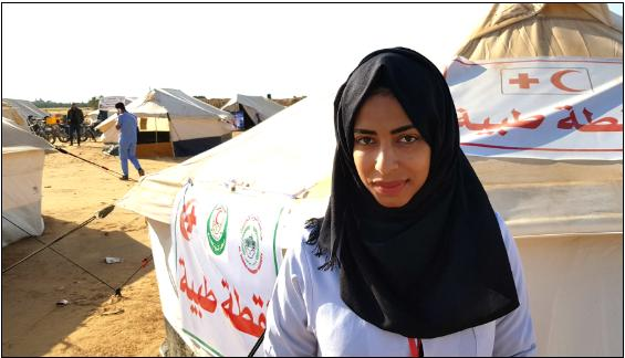 Rula a-Najar, 20, a nursing student from Khuza'ah and volunteer with a non-profit organization that provides medical care stands in front of a clinic tent not far from the Gaza border.
