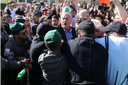 Israeli police accost the chairman of the High-Follow Up Committee for the Arab Citizens of Israel, former Hadash MK Muhammad Barakeh, during Monday's protest in Jerusalem.