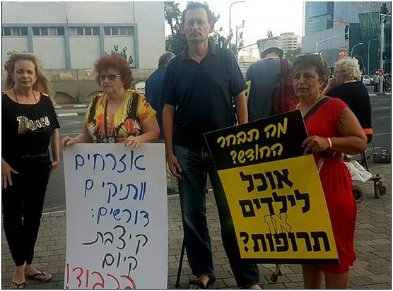 """MK Khenin with protesters in Tel Aviv on Thursday, May 31. The placard to the left reads: """"Senior citizens demand: Stipend that allows living honorably!""""; to the right"""" """"What will you choose this month? Food for children or medications?"""""""