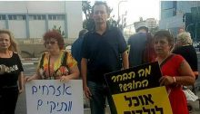 "MK Khenin with protesters in Tel Aviv on Thursday, May 31. The placard to the left reads: ""Senior citizens demand: Stipend that allows living honorably!""; to the right"" ""What will you choose this month? Food for children or medications?"""