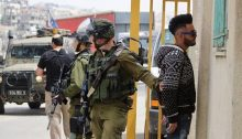 An Israeli soldier detains a Palestinian student at the entrance to the Al-'Arrub campus the Palestine Technical University, April 25, 2018.