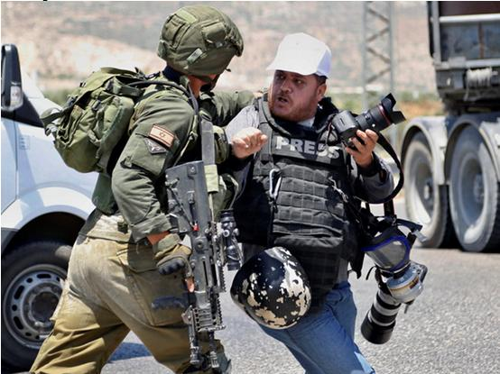 Occupation soldier accosts Palestinian photojournalist.