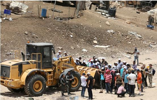 Protesters stand in path of a bulldozer near Khan al-Ahmar, on Wednesday, July 4.