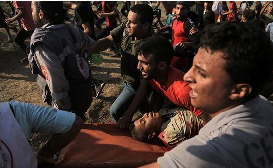 Palestinian paramedics and protesters evacuate Othman Hilles, 15, after he was mortally wounded by an Israeli sniper during the weekly frontier protests east of Gaza City, July 13, 2018.
