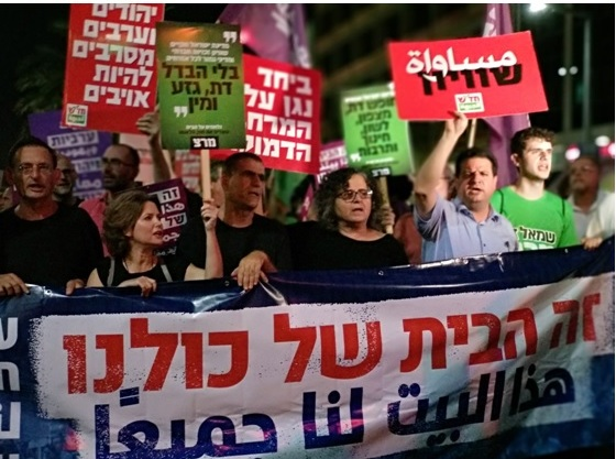 """From left to right: MKs Dov Khenin (Hadash), Michal Rozin (Meretz), Mossi Raz (Meretz), Aida Touma-Sliman (Hadash) and Ayman Odeh (Hadash) during the Saturday night protest march in Tel Aviv; the banner reads: """"This is home for all of us."""""""