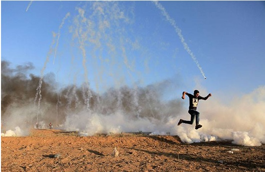 A Palestinian demonstrator runs for his life, last Friday, along the Israeli-Gaza border