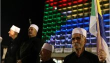 Elder religious leaders of the Druze community in Israel during the mass protest last Saturday night, August 4, at Rabin Square; in the background, the building of Tel Aviv's municipality is lit up with the colors of the Druze flag.