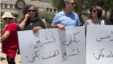 "MK Aida Touma-Sliman (second from left, in black) during a demonstration held in Nazareth to protest violence against the murder of women, May 17, 2018; the sign she's holding reads: ""Enough religious mandating of violence."""