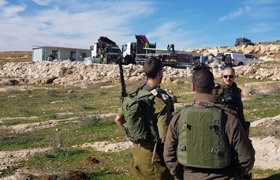"""Three armed Israeli soldiers of occupation, among others, """"secure"""" the site during the demolition of what was to be the new """"al-Tahadi 13"""" school, in the background, south of Hebron on Wednesday, December 5. The elementary school was to have opened its doors today, December 7, to 50 Palestinian pupils. (Photo: Ma'an)"""