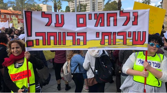 """""""Fighting for the Social Services!"""" — One of the banners held aloft by social workers during Thursday's mass demonstration at the Azrieli Junction, outside a major governmental office building in Tel Aviv."""