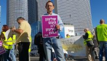 "Hadash MK Dov Khenin during the demonstration on Friday, December 14, at the Azrieli intersection in central Tel Aviv: ""Rule of the People, Not Rule of Capital"""