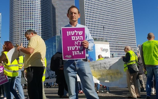 "Hadash MK Dov Khenin during the demonstration on Friday, December 14, at the Azrieli intersection in central Tel Aviv: ""Rule of the People, Not the Rule of Capital"""