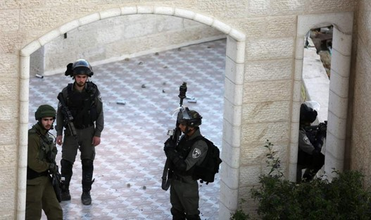 Israeli border police in the offices of the Palestinian news agency Wafa during their raid on December 10; empty tear gas canisters and other spent ammunition can be seen on the floor of the balcony of the offices.
