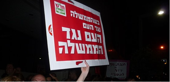 """""""When the government is against the people, the people are against the government,"""" a Hadash placard held aloft during last Saturday night's """"Yellow Vests"""" protest in Tel Aviv"""