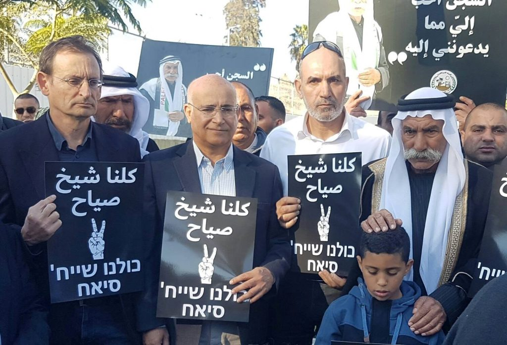 """Sheikh Sayeh Abu-Madi'am (first from right) is accompanied by hundreds of supporters before his entrance into Ramle's Ma'asiyahu prison on Tuesday to begin serving a 10-month sentence for trespassing on his own land. MK Dov Khenin (Hadash, first from left) is holding one of the """"We are all Sheikh Sayeh"""" placards distributed to demonstrators"""
