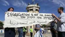 "Jewish American peace activists display a banner in English, Hebrew and Arabic reading, ""Segregation is not our Judaism,"" nearby the Israeli settlement in Hebron."