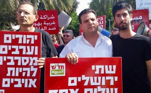 "Hadash MKs Dov Khenin, left, and Ayman Odeh (Chair of the Joint List), center, in a demonstration held in Central Tel Aviv on October 9, 2015. Khenin's placards reads: ""Jews and Arabs refuse to be enemies."""