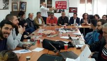 "Hadash electoral committee meeting last weekend to launch the party's campaign for the upcoming general elections for the 21st Knesset; the red placard held up in the background reads ""Opposing Fascism."""