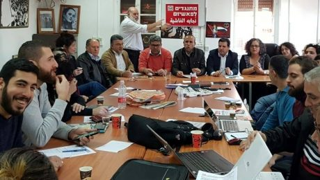 """Hadash electoral committee meeting last weekend to launch the party's campaign for the upcoming general elections for the 21st Knesset; the red placard held up in the background reads """"Opposing Fascism."""""""