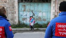 Two observers from the staff of the TIPH monitor the well-being of Palestinian children on their way to school in Hebron.