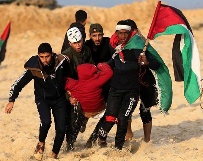 A Palestinian youth wounded by Israeli forces along the Gaza border is evacuated by other young protestors.