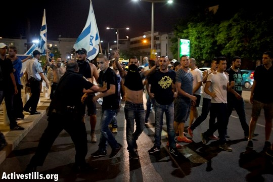 Lehava-Kach members attacking a demonstration against Israel's brutal Protective Edge military campaign in Gaza that was held at the Habima Square, Tel Aviv, July 2014 (Photo: Activestills)