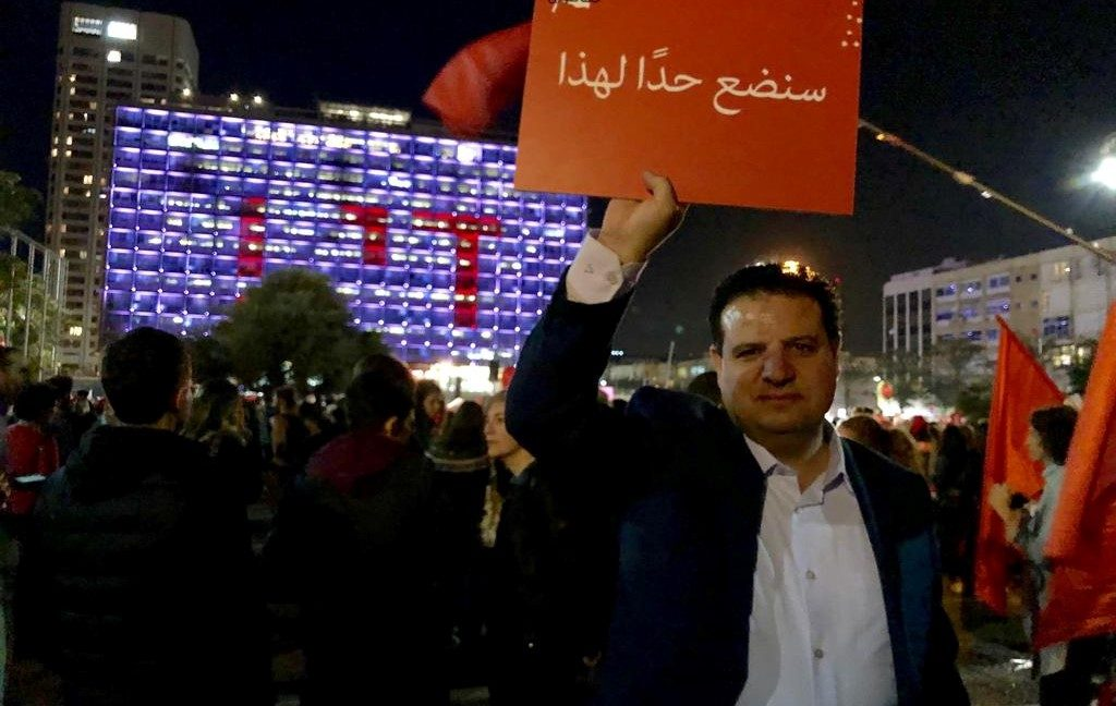 "MK Ayman Odeh during a demonstration against the murder of women in Tel-Aviv, December 4, 2018; the sign he holds aloft reads: ""We will put an end to this."""