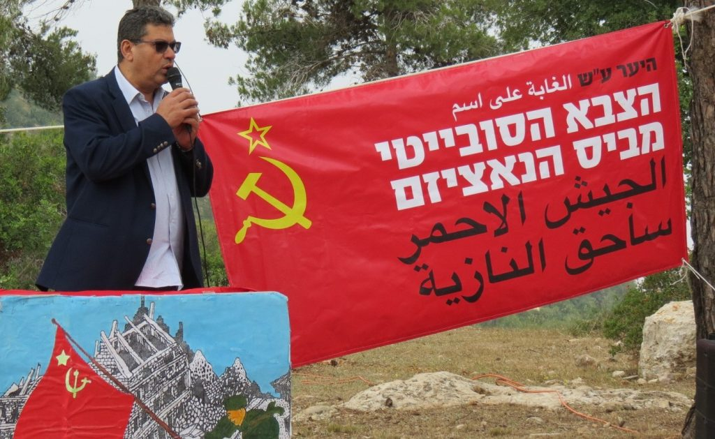 "CPI General Secretary, Adel Amer, during the last year's celebration of the Victory Day at the Red Army Forest near Jerusalem. The banner in Hebrew and Arabic reads: ""The forest named after the Soviet (Red) Army, Vanquisher of Nazism"""