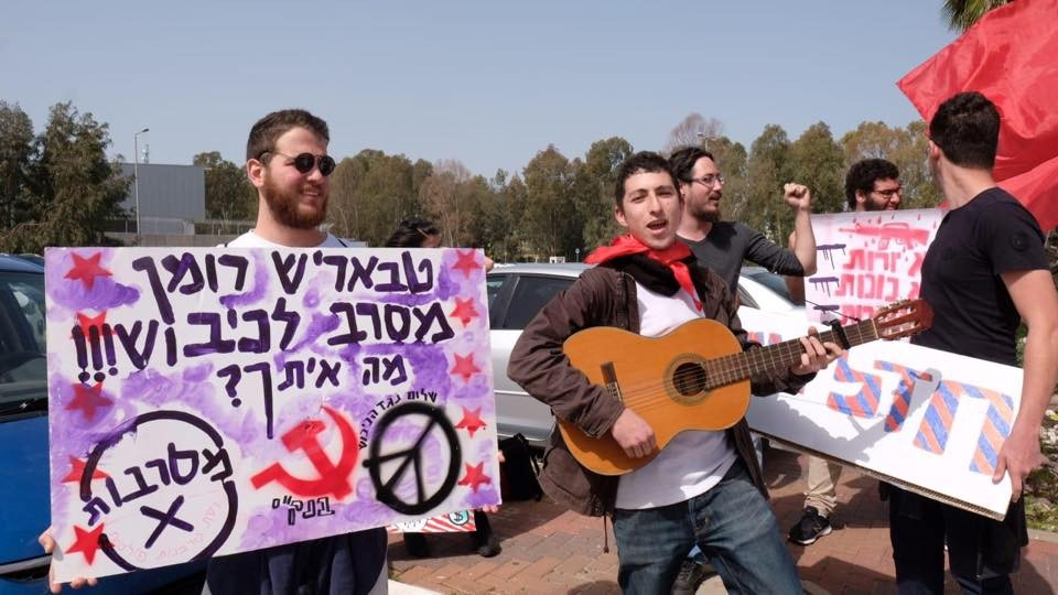 "Roman Levin (with guitar) and comrades demonstrate outside the military base at Beit Naballah. The Hebrew placard to the left reads: ""Tbarish ('Friend' ['Comrade'] in Russian), Roman rejects the occupation!!! What about you?"""