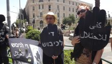 "Women in Black holding a Friday protest vigil at Paris Square in central West Jerusalem, near the official residence of the Prime Minister; the black placards in the shape of a stop sign read ""End the Occupation"" in Arabic and Hebrew."