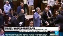 MKs from the Joint List vociferously protest the proceedings of the Knesset session during which Israel's parliament voted to pass the racist Nation-State Law in its second and third readings, enacting it as law, July 18-19, 2018.