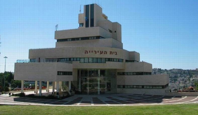 The municipal building of Upper Nazareth, now known as Nof Hagalil, which overlooks Arab Nazareth, in the background.