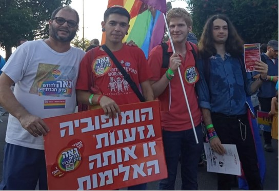 "Hadash MK Ofer Cassif, left, with Young Communist League activists at the Gay Pride Parade held last week in Rehovot; the placard reads: ""Homophobia [and] Racism are the same violence."""