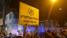 "Demonstrators in front of the Petah Tikva police station, on Friday night, August 16; the protestor's sign reads: ""Mendelblit's Police – Petah Tikva Station."""