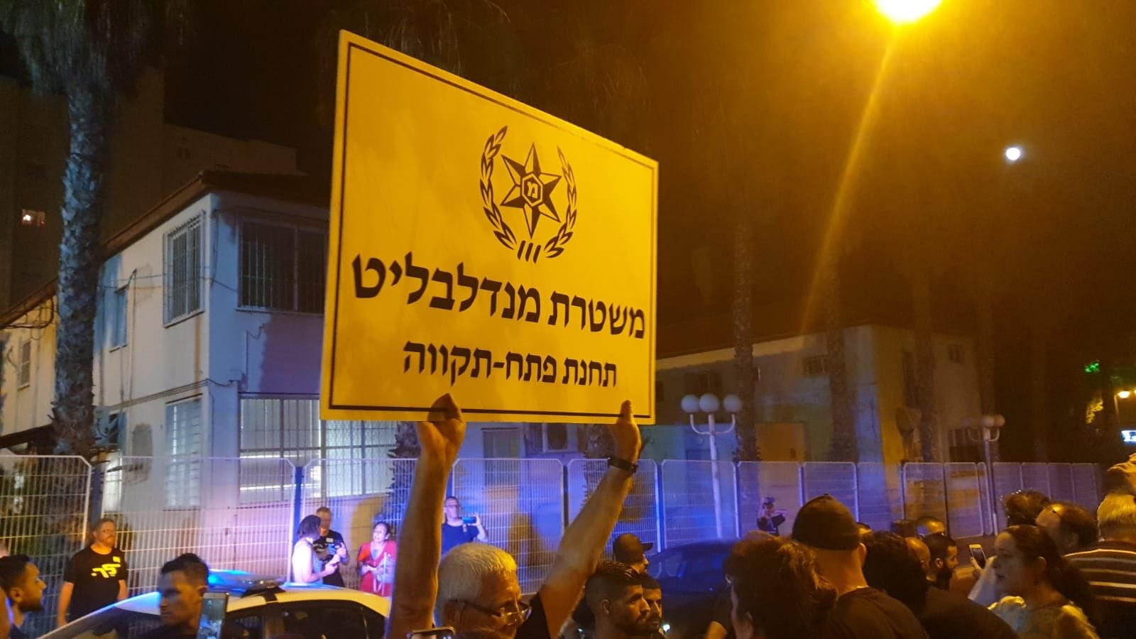 """Demonstrators in front of the Petah Tikva police station, on Friday night, August 16; the protestor's sign reads: """"Mendelblit's Police – Petah Tikva Station."""""""