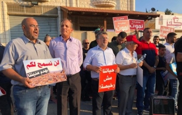 "Hadash demonstrators on Saturday, September 21, opposite the police station in Umm al-Fahm in northern Israel. Among the demonstrators, in the center holding orange and white placard is Hadash MK Yousef Jabareen, a resident of the city, whose sign reads: ""Our lives are not cheap!"" The sign held by the demonstrator in the left of the picture declares: ""We will never forgive you for destroying our city."" Other protests were held in Kafr Yasif in the western Galillee where Edib Dirawi, 38, the first of Friday's four shooting victims was murdered a day earlier and in Jisr az-Zarka along the Mediterranean coast between Haifa and Tel Aviv."