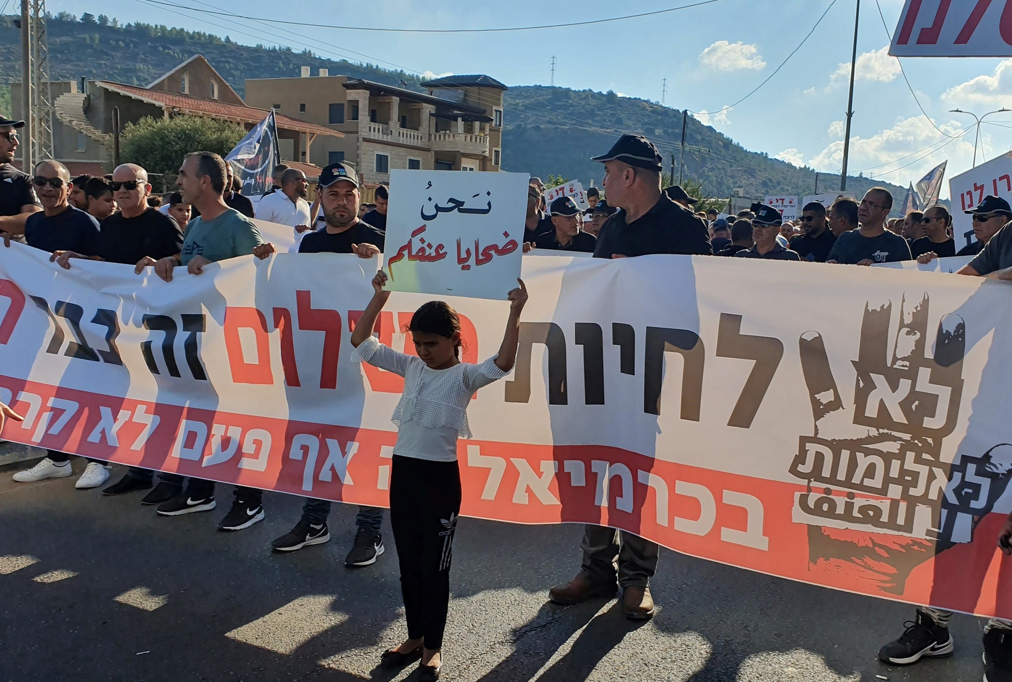 "Demonstrators marching in the Upper Galilee town of Majd al-Krum on Thursday, October 3, to protest rampant gangland violence in Israel's Arab communities and police inaction in combating it; the large banner reads (in Hebrew): ""No to Violence – To live in peace has become a dream... In Karmiel [a neighboring, primarily Jewish city just to the east of Majd al-Krum] this has never happened.""Before the banner, a young girl holds aloft a sign in Arabic reading: ""We are victims of your violence."""