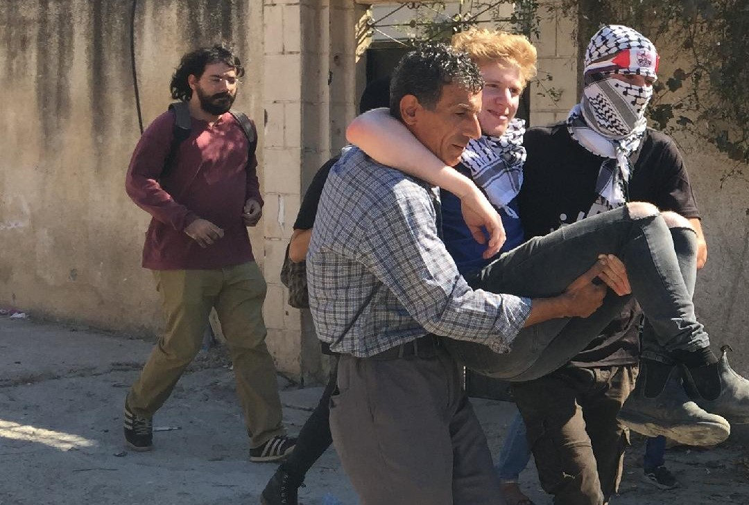 One of the two Israeli Communist demonstrators injured at Kafr Qaddum is evacuated by Palestinians, last Friday October 4.