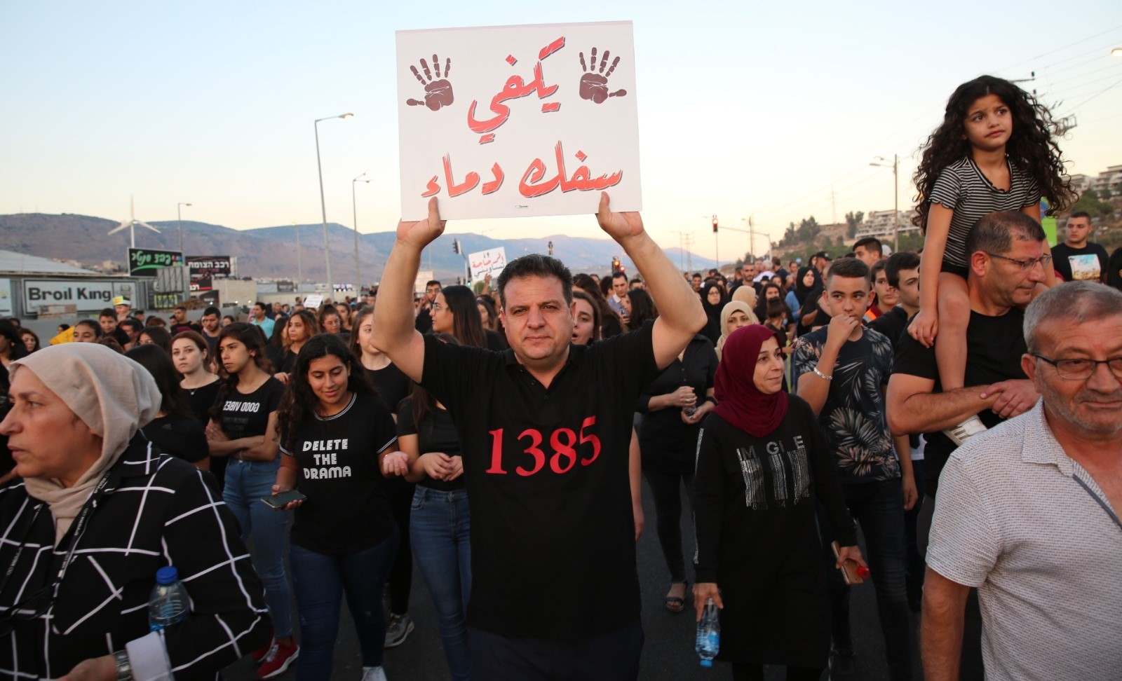 "MK Ayman Odeh during the demonstration against violence, last Tuesday in Majd al-Krum; the sign he's holding aloft reads ""Enough bloodshed."" The number 1385 on his shirt is the toll of Arab citizens of Israel who have died since the year 2000 as a result of violence."