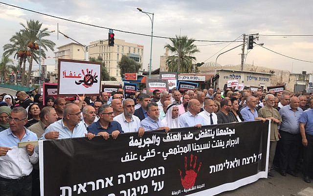 "Hundreds of demonstrators gathered in the central city of Ramle on Tuesday, October 15, to protest the wave of violence being unaddressed by police. The large banner reads (in Arabic): ""Our society is rising up against violence and crime. The[se] crimes are unraveling our social fabric – Enough violence""; (in Hebrew) ""Enough murder and violence; the police are responsible for defeating crime."" The banner is signed, beneath the bloodied hand print, by the ""Popular Committee – Ramle."""