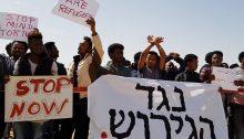 "African asylum seekers demonstrate in Tel Aviv against deportation, June 2018; the large banner in Hebrew reads ""Against Deportation."""