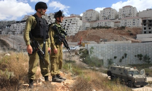 Occupation soldiers standing on the periphery of the West Bank settlement of Beitar Illit, which was partially built on land expropriated from the Palestinian village of Wadi Fukin