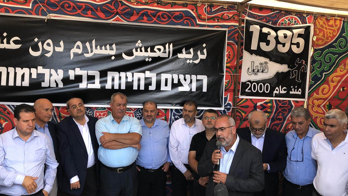 "MK Ayman Odeh (first from left), last Monday, November 4, with Joint List MKs inside the protest tent set up nearby the Prime Minister's Office in Jerusalem to call for tangible governmental action against violence and crime in the Arab community; the large banner at the left reads ""We want to live without violence and crime."" The banner to the right reads: ""1,395 fatalities since the year 2000."""