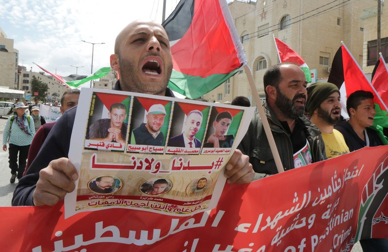 """Palestinians march during a demonstration in the West Bank city of Bethlehem in April, 2017, in which they called on Israel to return the bodies of slain Palestinian militants to their families. The headline in the poster reads: """"#We Want Our Children."""""""